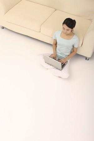 Woman sitting on the floor, using laptop Stock Photo