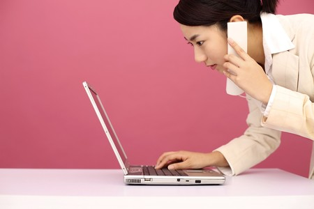 Woman talking on the phone while using laptop Stock Photo - 4194241