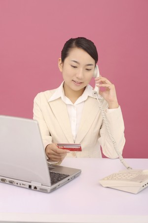 Woman referring to credit card while talking on the phone photo