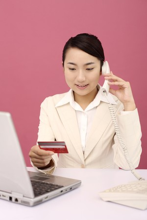 Woman referring to credit card while talking on the phone Stock Photo - 4194579