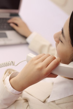 Woman talking on the phone while using laptop photo