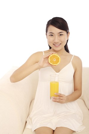 Woman holding a glass of orange juice and halved orange photo