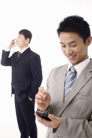 Businessman using PDA phone, another businessman talking on the phone in the background photo
