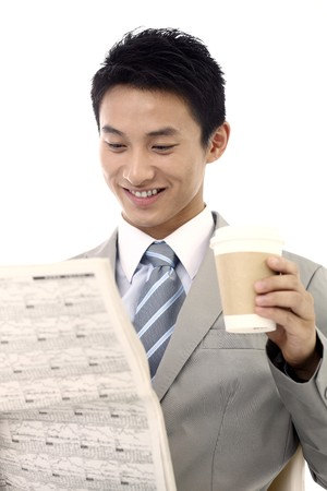 Businessman drinking coffee while reading newspaper photo