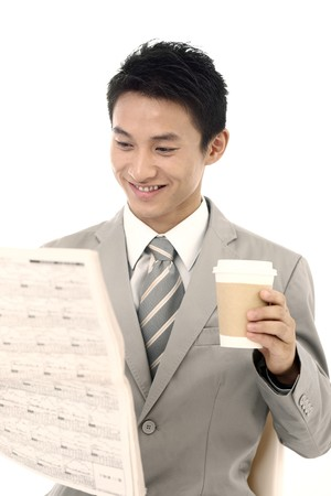 necktie: Businessman drinking coffee while reading newspaper