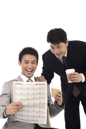 Businessmen laughing while reading newspaper together photo