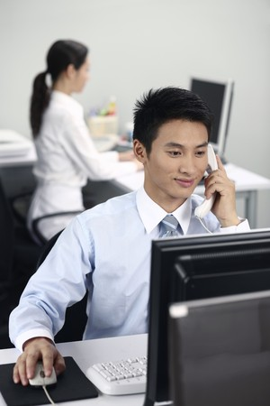 Businessman using computer while talking on the phone photo