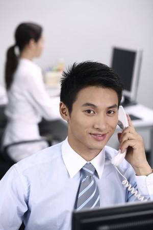 answering phone: Empresario sonriente al responder llamada telef�nica Foto de archivo