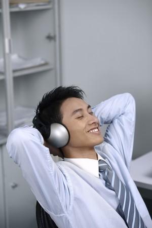 Businessman listening to music on the headphones photo