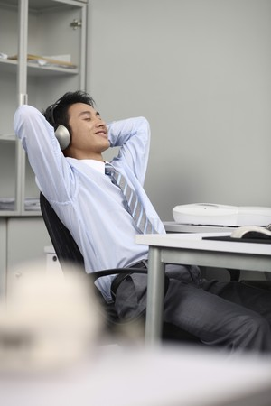 Businessman listening to music on the headphones Stock Photo - 4194613