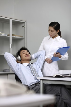 Businessman listening to music on the headphones, businesswoman looking at him photo
