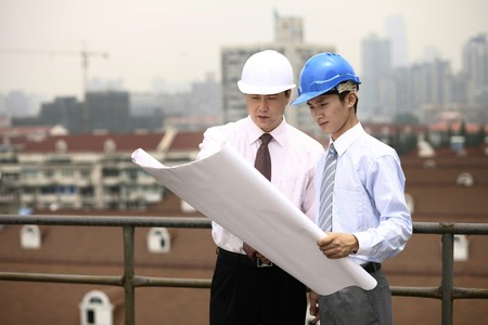 asian architect: Businessmen having discussion while looking at blueprint