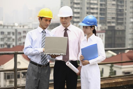 Business people having discussion, looking at laptop