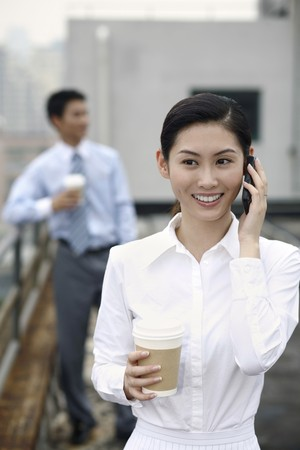 Businesswoman talking on the phone, businessman standing in the background photo