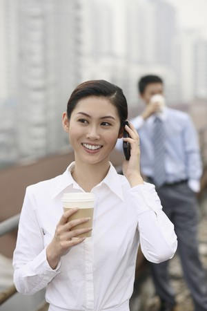 Businesswoman talking on the phone, businessman drinking coffee in the background photo