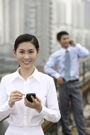 Businesswoman using PDA phone, businessman talking on the phone in the background photo