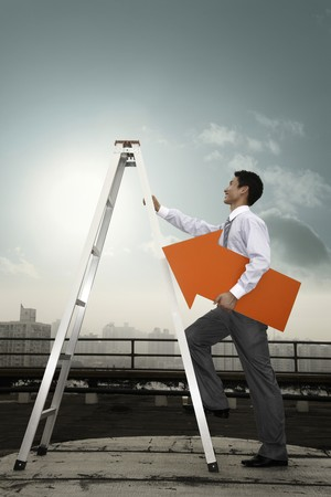 Businessman holding an arrow showing up while climbing up ladder