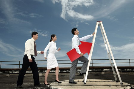 ladder of success: Business people queueing in a line to climb up a ladder Stock Photo