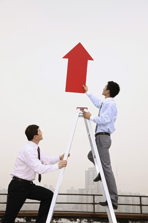 Businessman holding an arrow showing up while standing on ladder, another businessman watching from bottom
