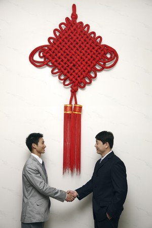 Businessmen shaking hands under a giant Chinese New Year decoration Stock Photo - 4194715