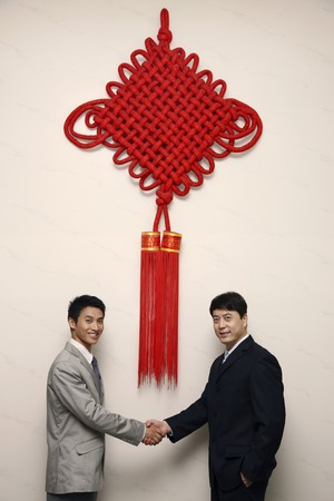 Businessmen shaking hands under a giant Chinese New Year decoration photo
