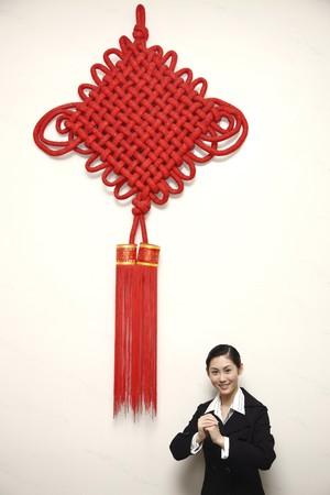 Businesswoman avec le geste de salutation, debout dans le cadre d'un g�ant de la d�coration du Nouvel An chinois Banque d'images - 4194588