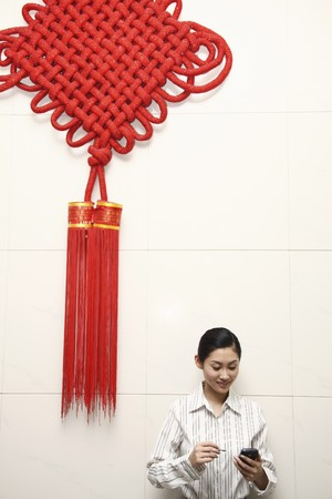Businesswoman using PDA phone, standing under a giant Chinese New Year decoration photo