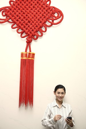 Businesswoman using PDA phone, standing under a giant Chinese New Year decoration Stock Photo - 4194656