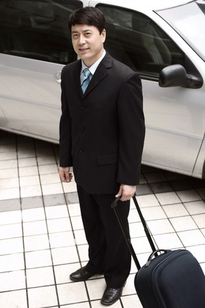 Businessman holding luggage next to car Stock Photo - 4194584