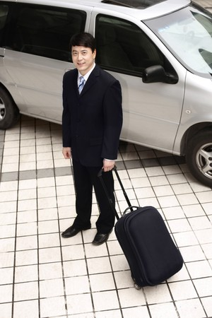 Businessman holding luggage next to car Stock Photo - 4194597