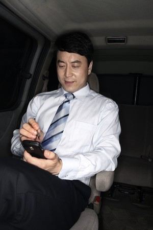 Businessman using PDA phone while traveling in the car Stock Photo - 4194731