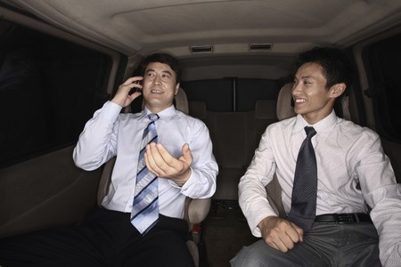 Businessman talking on the phone while traveling in the car, another businessman watching Stock Photo - 4194778