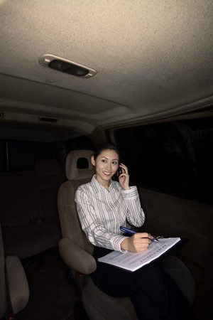 Businesswoman talking on the phone while traveling in the car photo