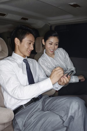 Businessman showing the message in his PDA phone to businesswoman photo