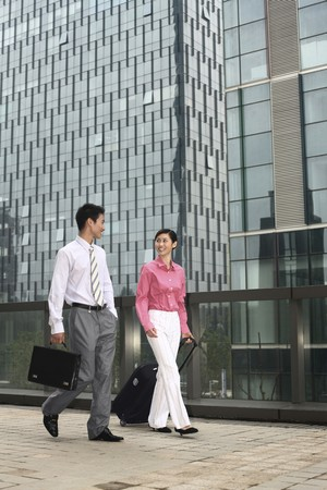 Businessman and businesswoman chatting while walking Stock Photo - 4194780
