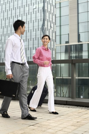 Businessman and businesswoman chatting while walking photo