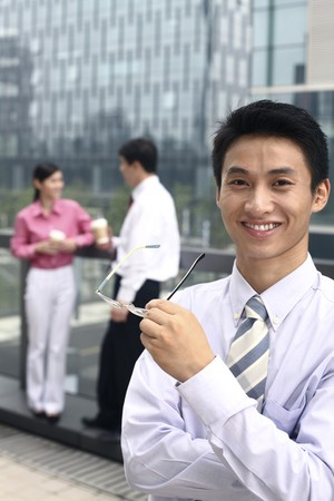 business woman standing: Businessman smiling while holding spectacles, business people chatting in the background