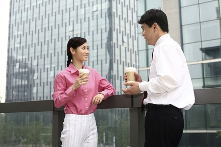 Businessman and businesswoman drinking coffee while chatting photo