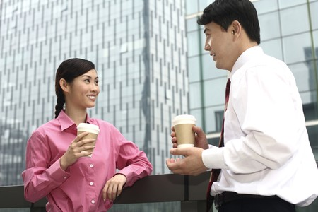 Businessman and businesswoman drinking coffee while chatting Stock Photo - 4194665
