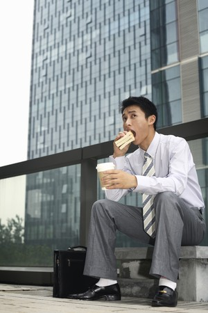 Businessman having sandwich and hot coffee as breakfast photo