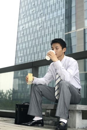 Businessman having sandwich and hot coffee as breakfast Stock Photo - 4194768