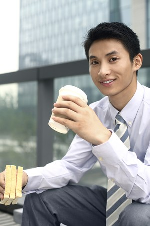 Businessman having sandwich and hot coffee as breakfast Stock Photo - 4194733