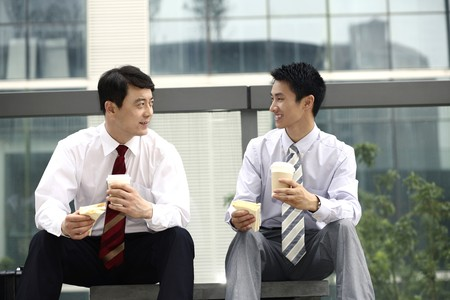 only mid adult men: Businessmen having sandwich and hot coffee as breakfast