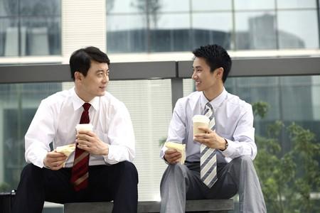 Businessmen having sandwich and hot coffee as breakfast Stock Photo - 4194757