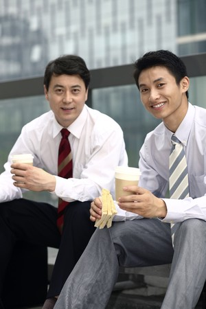 Businessmen having sandwich and hot coffee as breakfast Stock Photo - 4194726