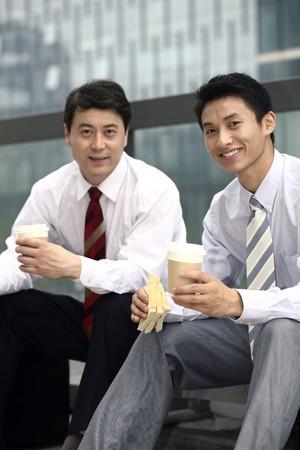 Businessmen having sandwich and hot coffee as breakfast Stock Photo - 4194726