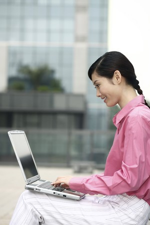Businesswoman smiling while using laptop Stock Photo - 4194690