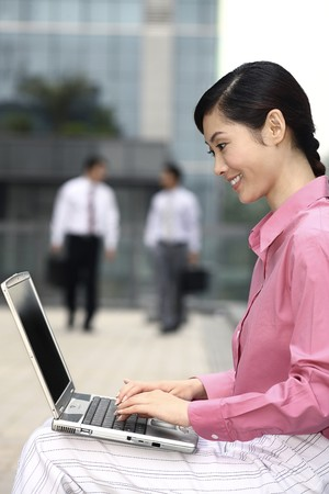 Businesswoman smiling while using laptop, businessmen walking in the background photo