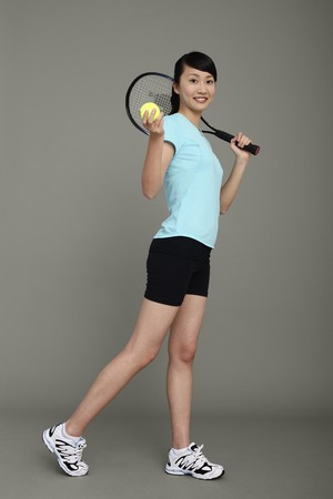 tennis racket: Woman holding tennis racket and tennis ball