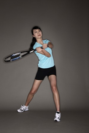 tennis racket: Woman swinging tennis racket